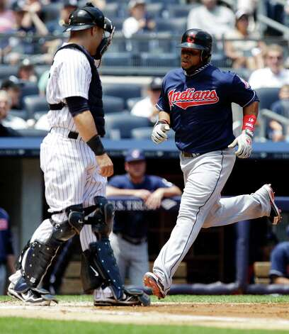 Cleveland Indians' Carlos Santana scores on a hit by teammate Shelley Duncan during the second inning of a baseball game as New York Yankees catcher Russell Martin looks on Wednesday, June 27, 2012, in New York. (AP Photo/Frank Franklin II) Photo: Frank Franklin II