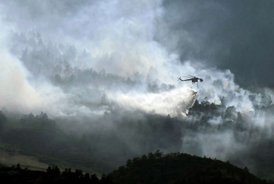 A helicopter battles the Waldo Canyon Fire by Air Force Academy on Wednesday, June 27, 2012, near Co