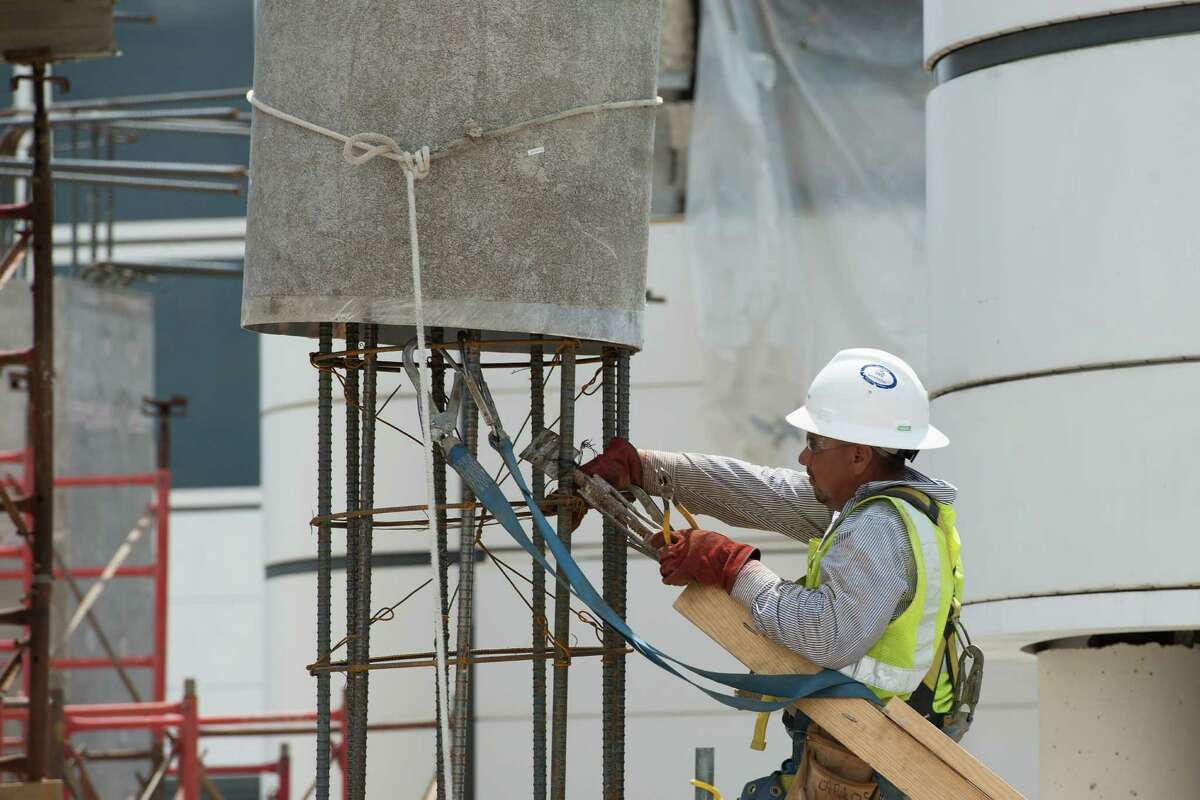 Workers set foundations for the jet bridges being installed at Terminal D.