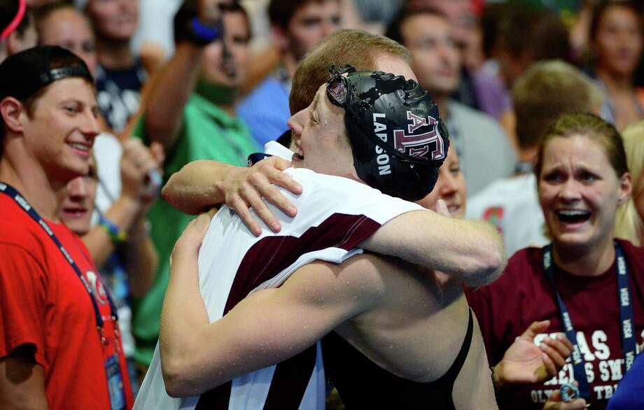 Breeja Larson, right, hugs Texas A&M head swim coach Steve Bultman after winning the women's 100-meter breaststroke final at the U.S. Olympic swimming trials, Wednesday, June 27, 2012, in Omaha, Neb. (AP Photo/Mark J. Terrill) Photo: Associated Press