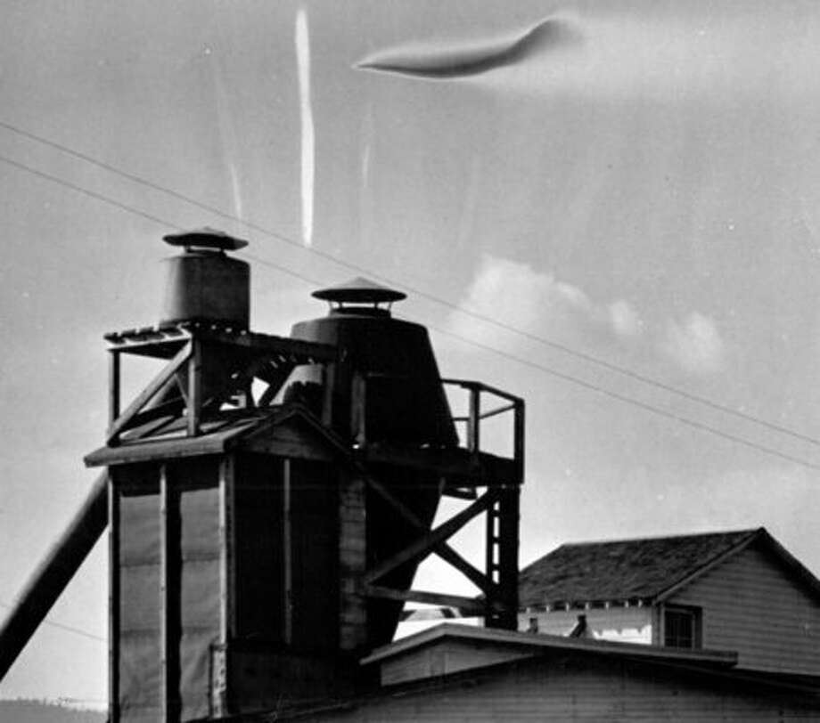 A suspected flying saucer photo from the P-I archive. This image was published in Aug. 1952 and taken by Walter Elliott of Anacortes, Wash. The vertical white line and others are marks on the original photo. (seattlepi.com file)