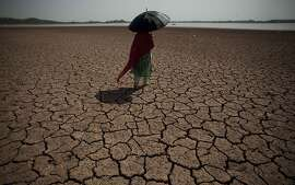 A Pakistani woman walks on a dry bank that provides water to Islamabad and Rawalpindi cities, at Rawal dam in Islamabad, Pakistan, Wednesday, June 27, 2012. The water level in dams and rivers are low due to dry and hot weather causing water and energy shortage to civilians. (AP Photo/B.K. Bangash)