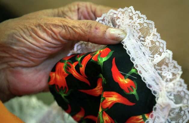 Clonie Glasco sews lace on flaming chili pepper fabric as she makes a hot place mat in the sewing class at the Claude Black Center.  Tuesday, June 26, 2012. Photo: BOB OWEN, San Antonio Express-News / © 2012 San Antonio Express-News