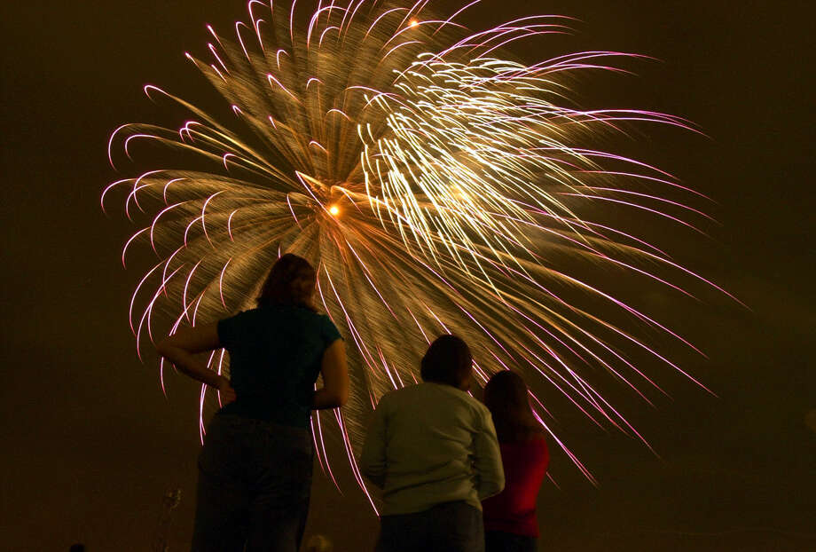 Fans watch big aerial fireworks — which are not subject to the county ban — at a Fiesta Oyster Bake past. Photo: Edward A. Ornelas, San Antonio Express-News