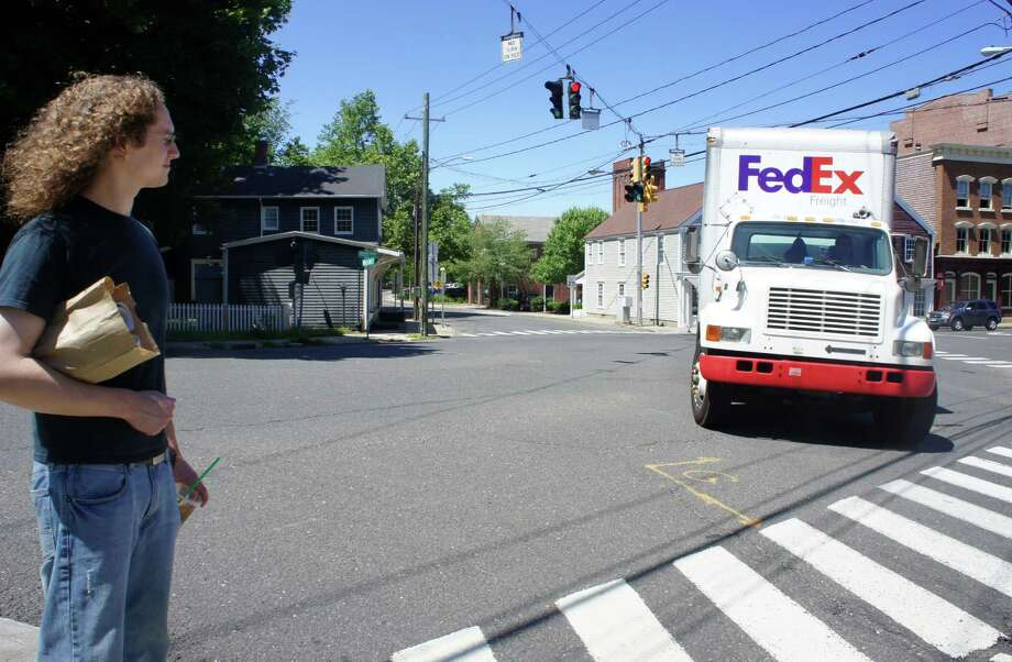 Brendan Dunne, a technician at TBI Computer on Post Road West, watches traffic at the intersection of Post Road West, Riverside Avenue and Wilton Road. Photo: Paul Schott / Westport News