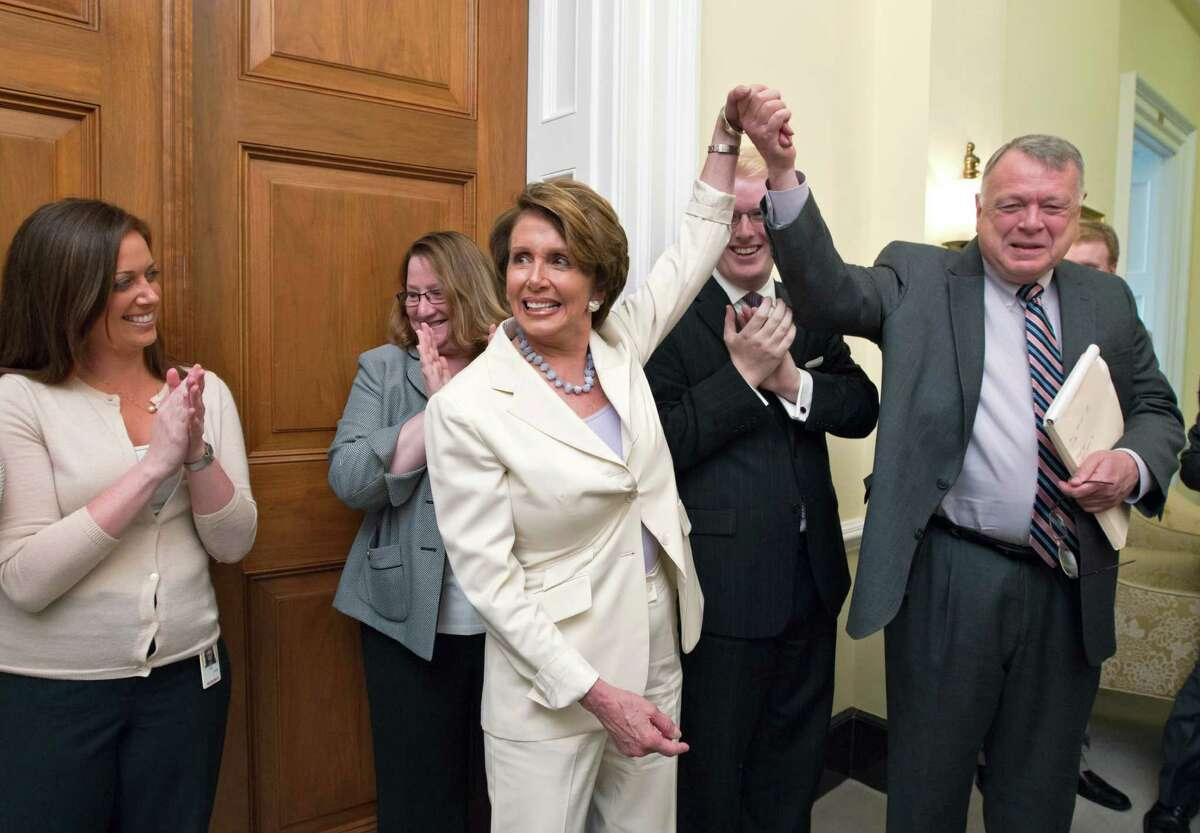House Minority Leader Nancy Pelosi of Calif. relays the breaking news to her staff that the Supreme Court had just upheld the Affordable Care Act, Thursday, June 28, 2012, on Capitol Hill in Washington. Pelosi, the former speaker of the House, was instrumental in helping to pass health care reform in Congress and was at President Obama's side when he signed it into law. At right, Pelosi gives credit to Wendell Primus, a senior policy adviser.