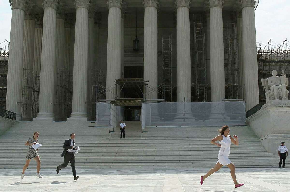 WASHINGTON, DC - JUNE 28: Reporters run with the U.S. Supreme Court's health care decision on June 28, 2012 in Washington, DC. Today the high court upheld President Obamas health care overhaul, in a victory for the president and Congressional Democrats.