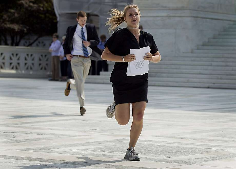 Journalists run out of the Supreme Court building after receiving the court's decision on the Affordable Care Act in Washington, D.C., U.S., on Thursday, June 28, 2012. The U.S. Supreme Court upheld the core of President Barack Obama's health-care overhaul, giving him an election-year triumph and preserving most of a law that would expand insurance to millions of people and transform an industry that makes up 18 percent of the nation's economy. Photographer: Andrew Harrer/Bloomberg Photo: Andrew Harrer, Bloomberg
