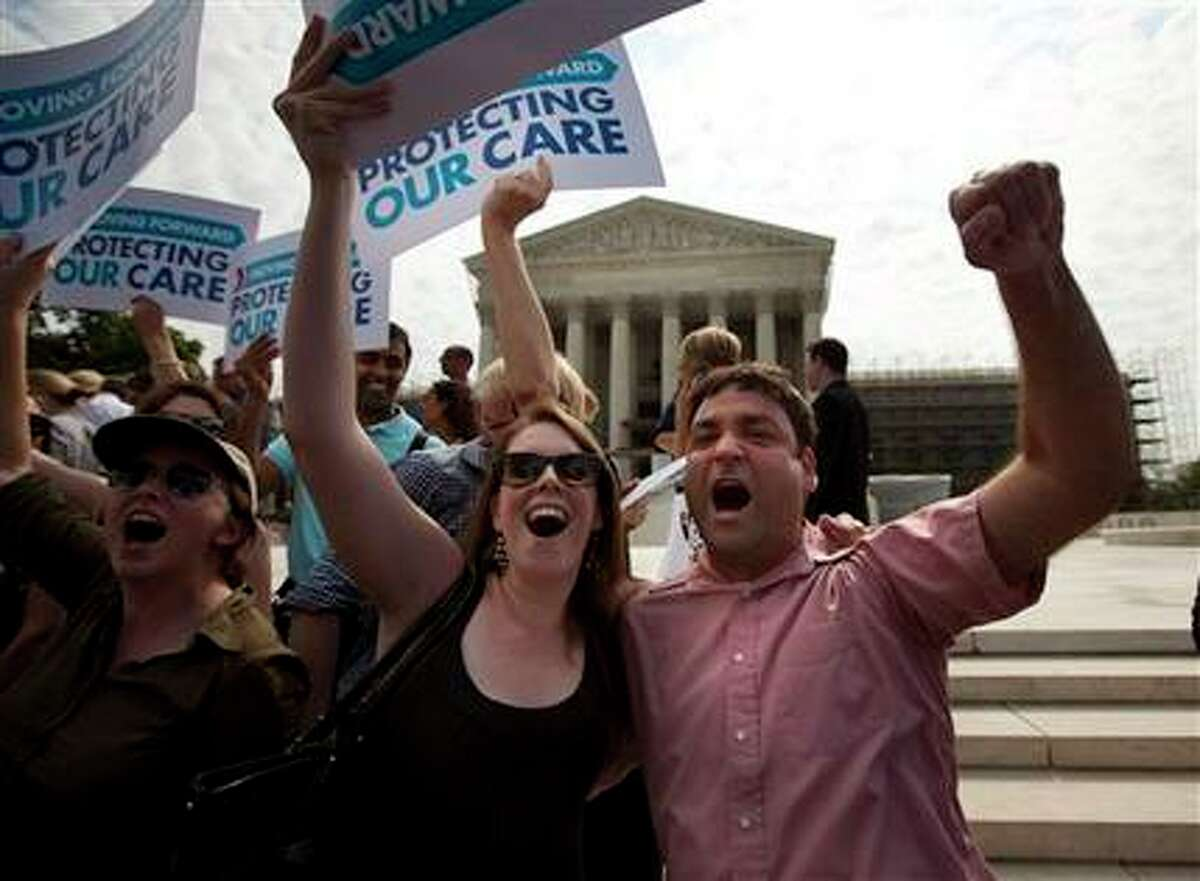 Claire McAndrew of Washington, left, and Donny Kirsch of Washington, celebrate outside the Supreme Court in Washington, Thursday, June 28, 2012, after the courts's ruling on health care. (AP Photo/Evan Vucci) ((AP Photo/Evan Vucci) / AP)