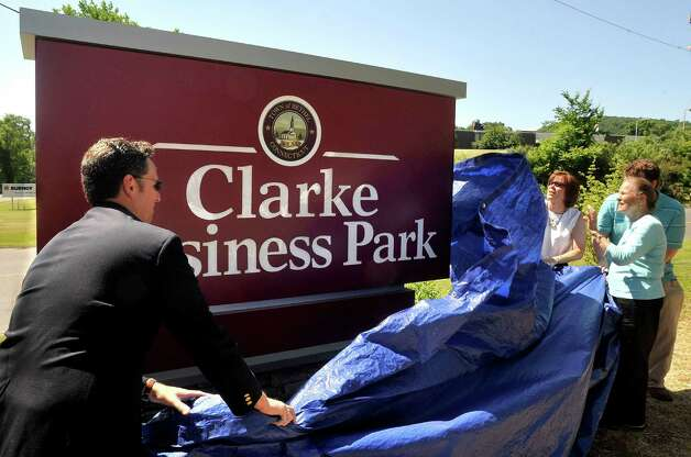 Brendan McCollam, left, and Kate Clarke Bush, second from right, unveil the sign rededicating the Francis J. Clarke Industrial Park as the Clarke Business Park in Bethel Thursday, June 28, 2012. Rose Ann Clarke, 79, looks on. Photo: Michael Duffy / The News-Times