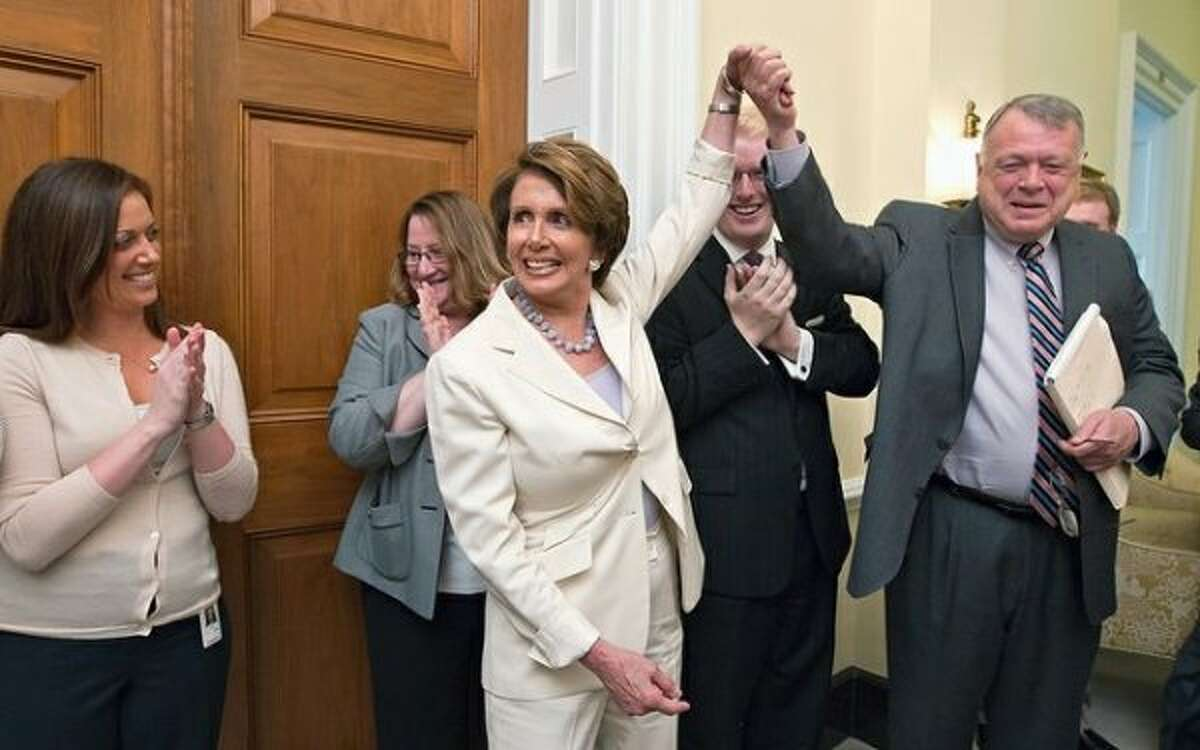 House Minority Leader Nancy Pelosi of Calif. relays the breaking news to her staff that the Supreme Court had just upheld the Affordable Care Act, Thursday, June 28, 2012, on Capitol Hill in Washington. Pelosi, the former speaker of the House, was instrumental in helping to pass health care reform in Congress and was at President Obama's side when he signed it into law. At right, Pelosi gives credit to Wendell Primus, a senior policy adviser ((AP Photo/J. Scott Applewhite))