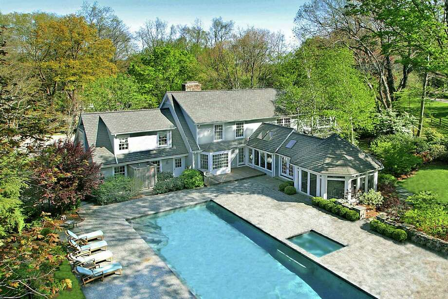 This 6,100-square-foot house at 45 Red Coat Road, Westport, features a bluestone patio, a 60-foot swimming pool and a two-acre yard. Photo: Contributed Photo