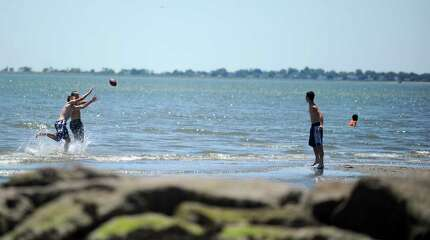 Dave Uhl, 17, of Beacon Falls, throws a football to friends Anthony Scirpo, left, and Brian Reis, Wednesday, June 27, 2012 at Silver Sands State Park in Milford, Conn.  The beach is closed due to poor water quality.  Rocky Neck State Park in Niantic is also closed and the east end of Sherwood Island State Park in Westport is closed.