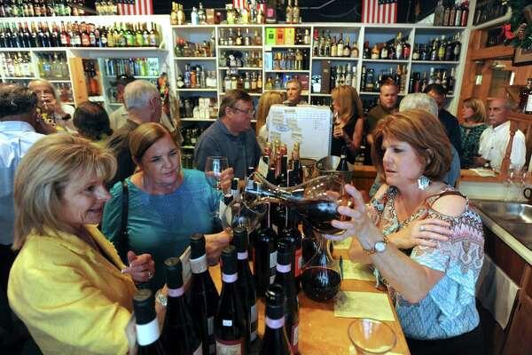 Kristene Bainbridge serves La Spinetta wine during a wine tasting at Joe Saglimbeni Fine Wines in San Antonio on June 21, 2012.