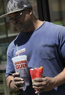 A man leaves a 7-Eleven store with a Double Gulp drink, in New York, Thursday, May 31, 2012. New York Mayor Michael Bloomberg is proposing a ban on the sale of large sodas and other sugary drinks in the city's restaurants, delis and movie theaters in the hopes of combating obesity, an expansion of his administration's efforts to encourage healthy behavior by limiting residents' choices. (AP Photo/Richard Drew)