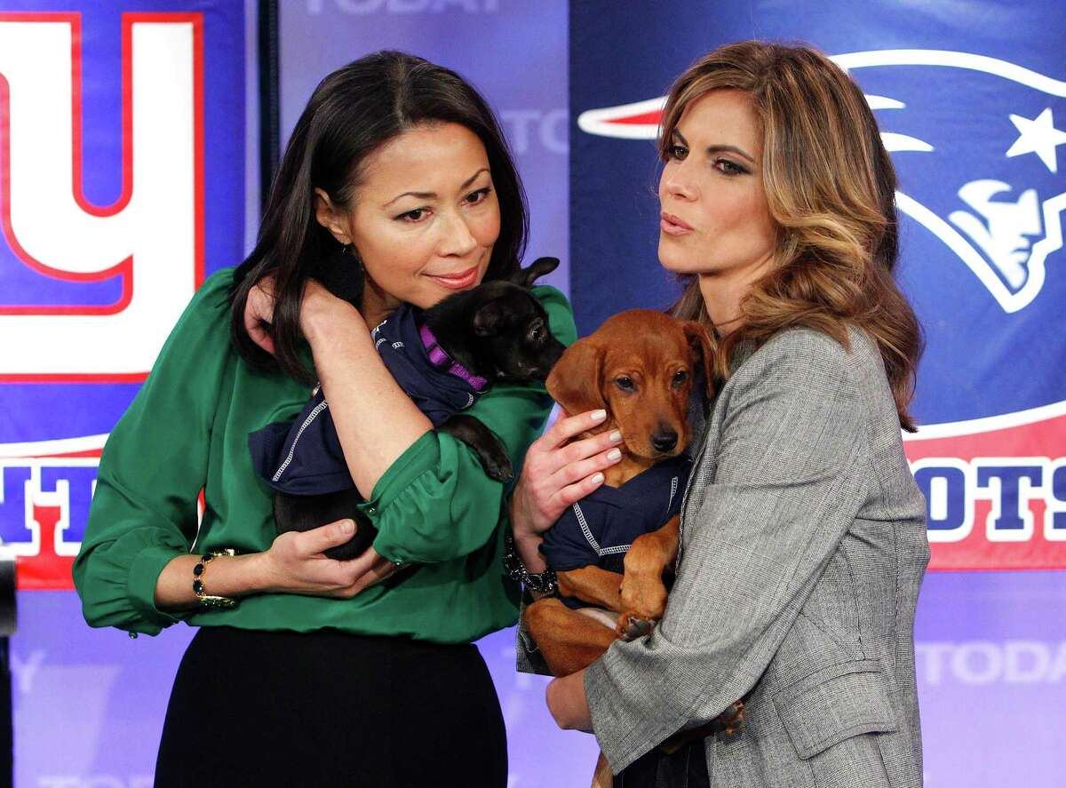 This Feb. 1, 2012 photo released by NBC shows co-hosts Ann Curry, left, and the Natalie Morales holding puppies just before a puppy bowl segment on the