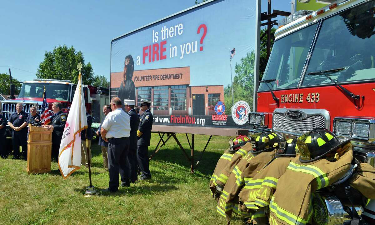 State and local fire officials hold a news conference in front of a billboard on Central Avenue in Colonie, Thursday June 28, 2012, rolling out a new advertising campaign to recruit volunteer firefighters statewide. (John Carl D'Annibale / Times Union)