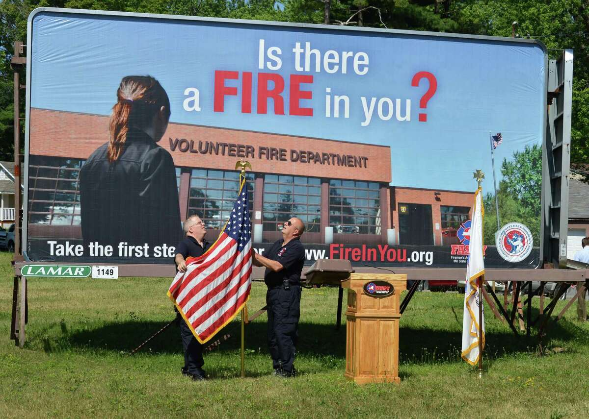 Stanford Heights fire fighters Paul Avery, left, and Garry Boomhower set up flags in front of a billboard on Central Avenue in Colonie Thursday June 28, 2012, for a news conference rolling out a new advertising campaign to recruit volunteer firefighters statewide. (John Carl D'Annibale / Times Union)