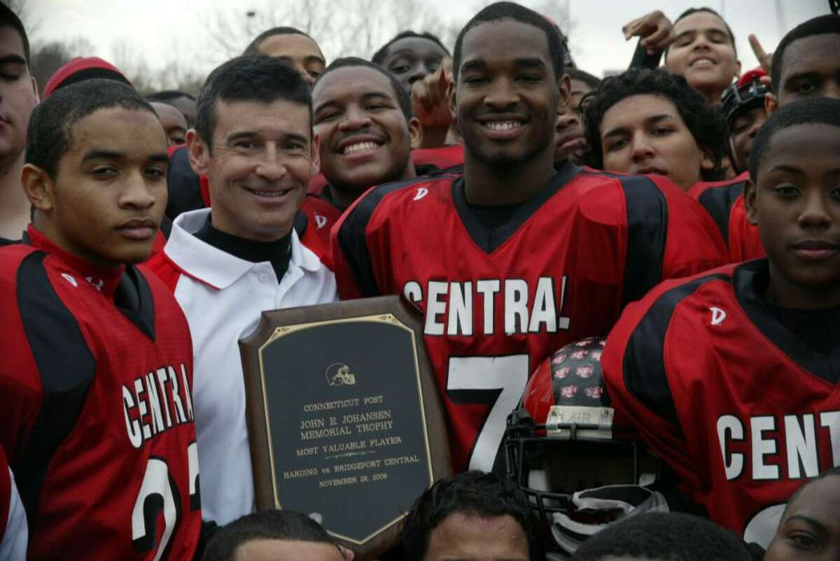 Central High School footbal coach, Dave Cadelina holds the John E. Johansen Memorial Trophy with the 2009 winner, Central's Quarterback Christon Gill after Central's 49-0 victory over Harding, Thursday, Nov. 26, 2009.