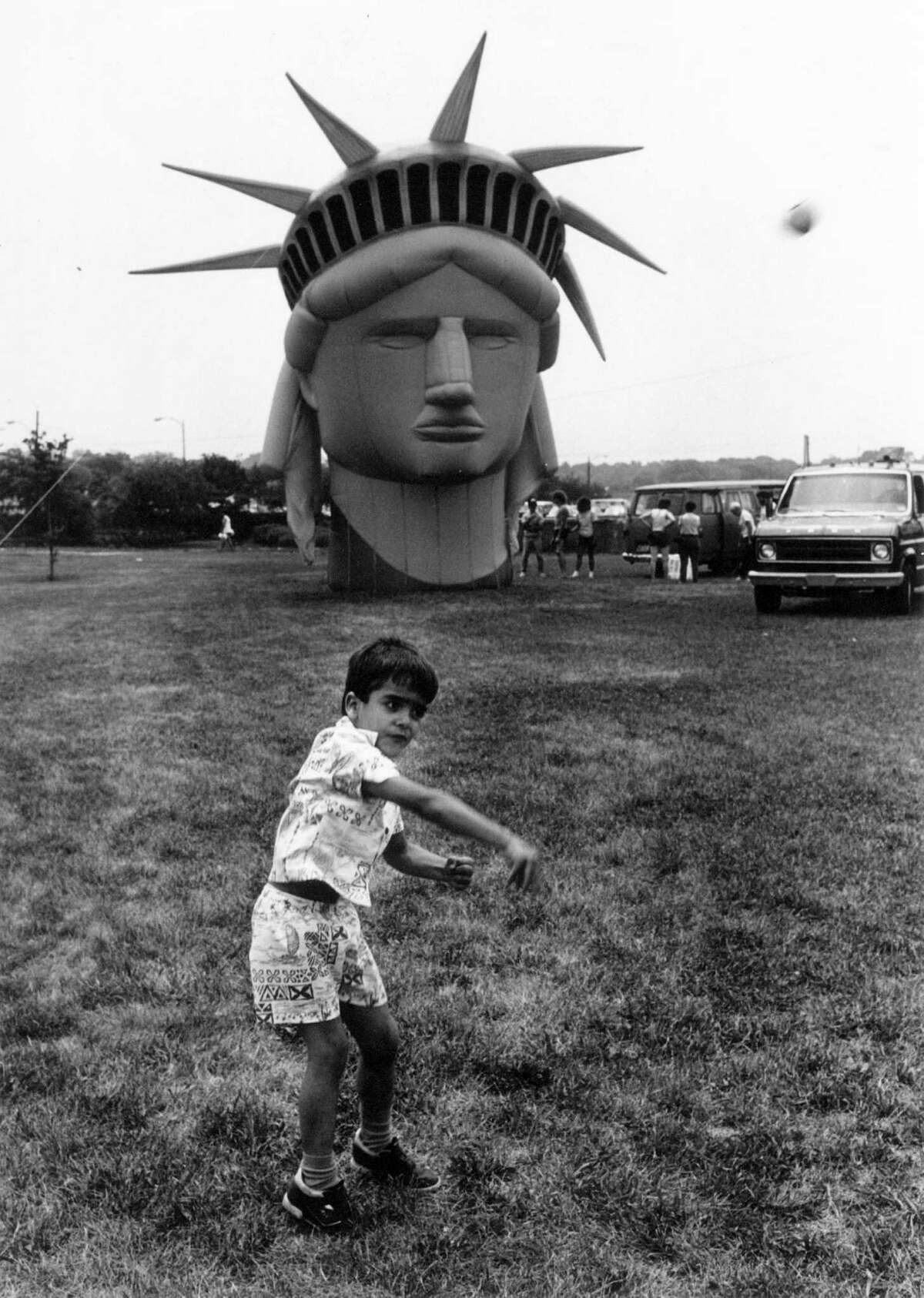 July 4, 1987: Carlos Lopez, 5, of Stamford frolics in Cummings Park in front of a balloon fasimile of the Statue of Liberty's head. The balloon was set to float above the park in the city's fourth of July celebration.