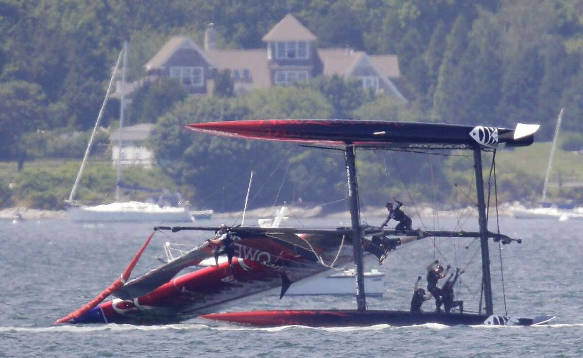 Team New Zealand crew members hang on as they attempt to right their ship after their boat capsized during a match race at the first day of the America's Cup World Series regatta in Newport, R.I., Thursday, June 28, 2012. (AP Photo/Stephan Savoia)