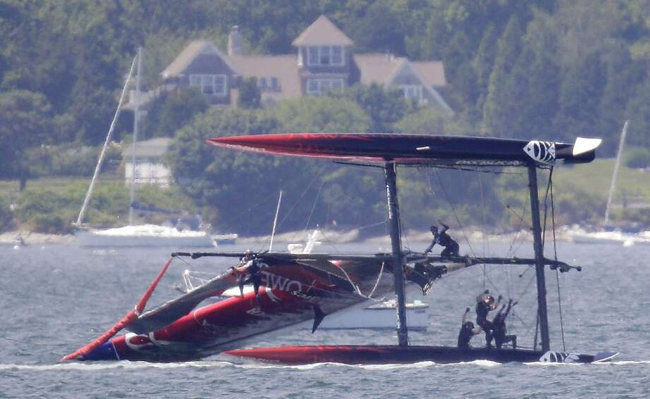 Team New Zealand crew members hang on as they attempt to right their ship after their boat capsized during a match race at the first day of the America's Cup World Series regatta in Newport, R.I., Thursday, June 28, 2012. (AP Photo/Stephan Savoia) Photo: Stephan Savoia, Associated Press