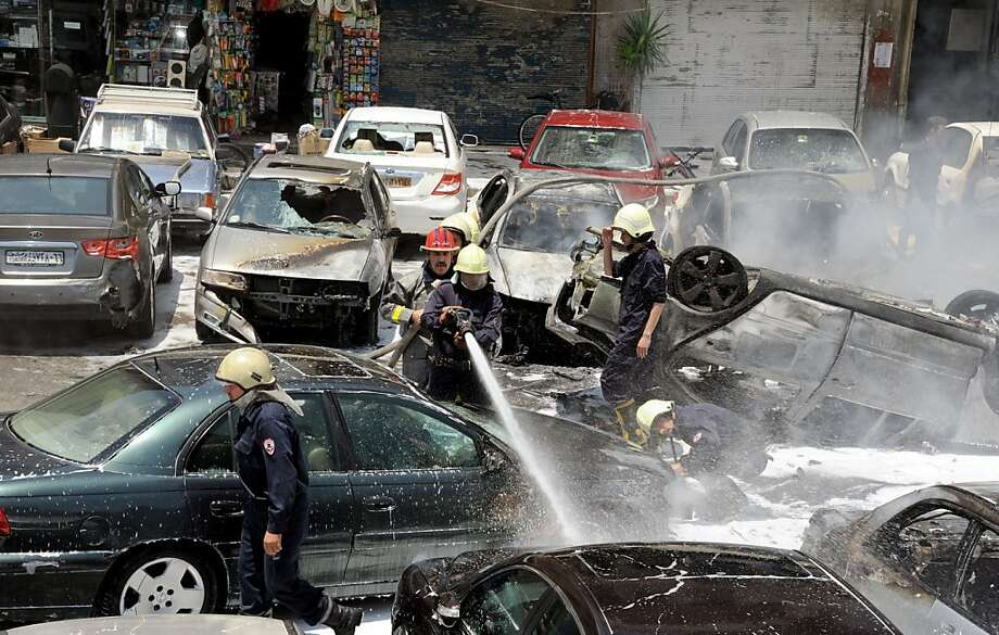 """A handout picture released by the official Syrian Arab news agency, SANA, shows a fireman spraying a car as they attempt to extinguish fires that broke out at the scene of two huge bomb explosions outside the Palace of Justice in Central Damascus on June 28, 2012.  A police source told AFP on condition of anonymity that two magnetic bombs exploded in two judges' cars in the open-air car park, while a third was in the process of being defused.  AFP PHOTO/HO/SANA   == RESTRICTED TO EDITORIAL USE - MANDATORY CREDIT """"AFP PHOTO / HO / SANA"""" - NO MARKETING NO ADVERTISING CAMPAIGNS - DISTRIBUTED AS A SERVICE TO CLIENTS ==-/AFP/GettyImages Photo: -, AFP/Getty Images"""
