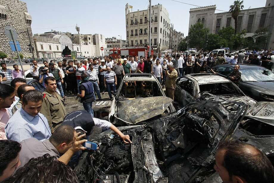 Syrians inspect burned cars at the site of a blast in the Syrian capital Damascus Thursday June 28, 2012. A strong explosion rocked the Syrian capital Thursday near a busy market and the Palace of Justice, sending black smoke billowing into the sky. State TV reported at least three people were wounded and around 20 cars were damaged. (AP Photo/Muzaffar Salman) Photo: Muzaffar Salman, Associated Press