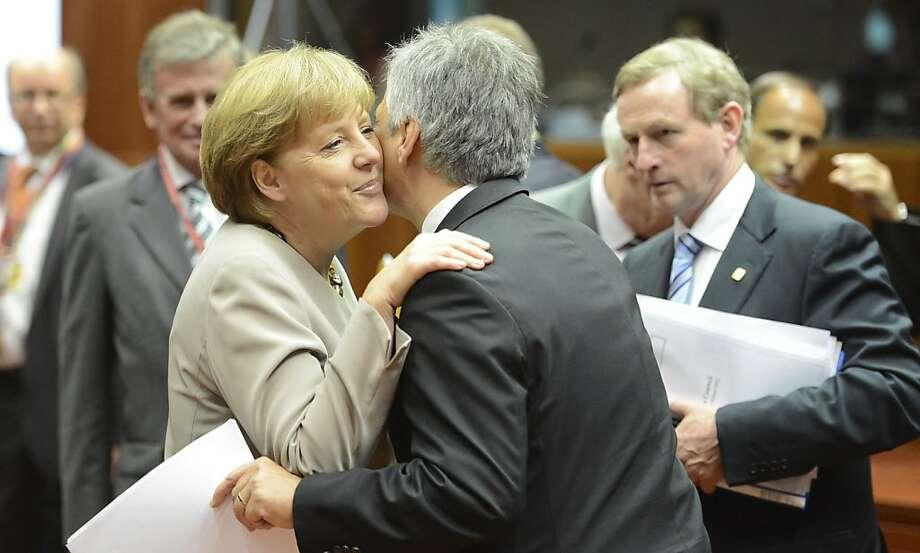 German Chancellor Angela Merkel, left, greets Austria's Chancellor Werner Faymann. Photo: Geert Vanden Wijngaert, Associated Press