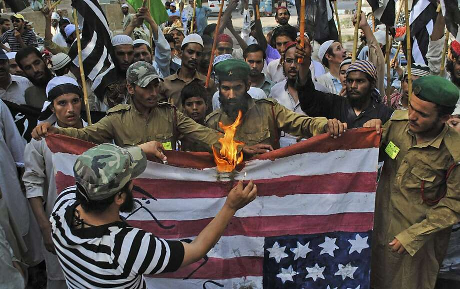 Supporters of Pakistani religious party Jamiat Ulema-e-Islam, burn a representation of a US flag during a rally condemning US drone strikes in tribal areas and the reopening of the NATO supply line to neighboring Afghanistan, in Hyderabad, Pakistan, Friday, June 15, 2012. (AP Photo/Pervez Masih) Photo: Pervez Masih, Associated Press
