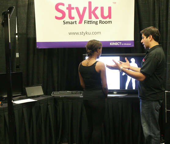 "Raj Sareen, right, founder and CEO of Styku, demonstrates his company's virtual fitting room technology at the Microsoft Accelerator for Kinect exhibition in Redmond on Thursday, June 28, 2012. ""People don't know what size to order,"" said Elizabeth Thomas, the company's vice president for marketing. ""It's one of the biggest barriers to online apparel sales."" The company plans to sell the system to retailers that have stores and online sales, and provide it free to consumers. A well-known retailer that the company cannot yet name plans to start a trial Aug. 6 in four fitting rooms in two stores. Photo: Aubrey Cohen/seattlepi.com Staff"