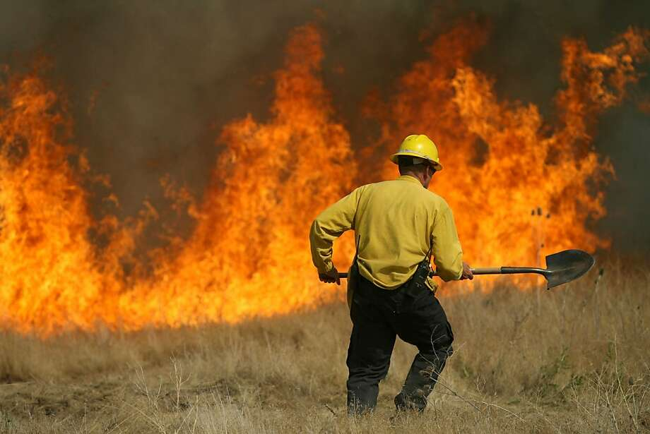 A member of the Rock Creek Rural Fire Protection District fights a fire near the Hidden Lakes subdivision on Wednesday, June 27, 2012 in Twin Falls, Idaho. (AP Photo/Times-News, Ashley Smith) Photo: Ashley Smith, Associated Press