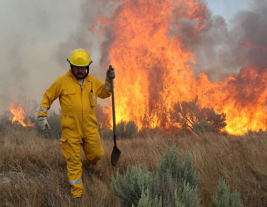 In this photo taken Wednesday, June 27, 2012, Todd Allison, a member Rock Creek Rural Fire Protection District re-positions while fighting a fire near the Hidden Lakes subdivision in Twin Falls, Idaho. (AP Photo/Times-News, Ashley Smith) Photo: Ashley Smith, Associated Press