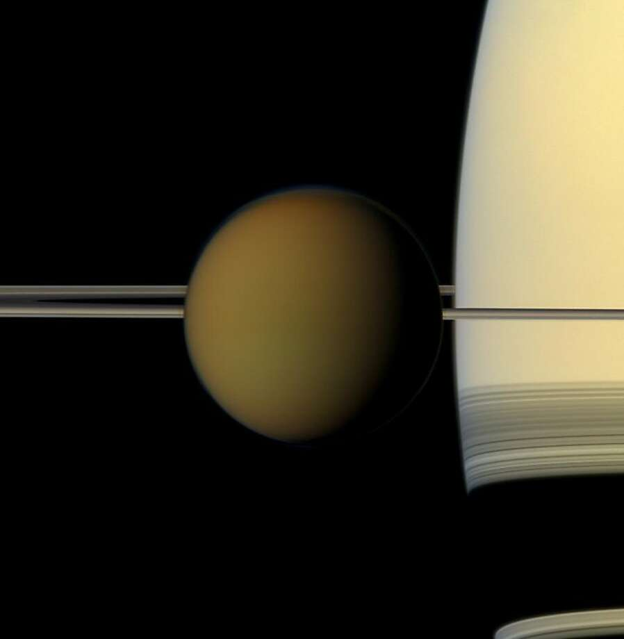 Saturn's largest moon, Titan, passing in front of the planet and its rings. Photo: Associated Press