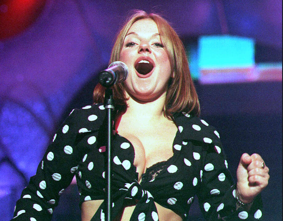 "Ginger Spice, Geri Halliwell, performing with the Spice Girls at London's Wembley Arena on April 4, 1998. Halliwell created s stir when she announced she was leaving the group on May 31, 1998. Halliwell cited ""differences"" for her reason for leaving, but wished the other four members continuing success. Photo: (AP Photo/Sean Dempsey/FILE)"