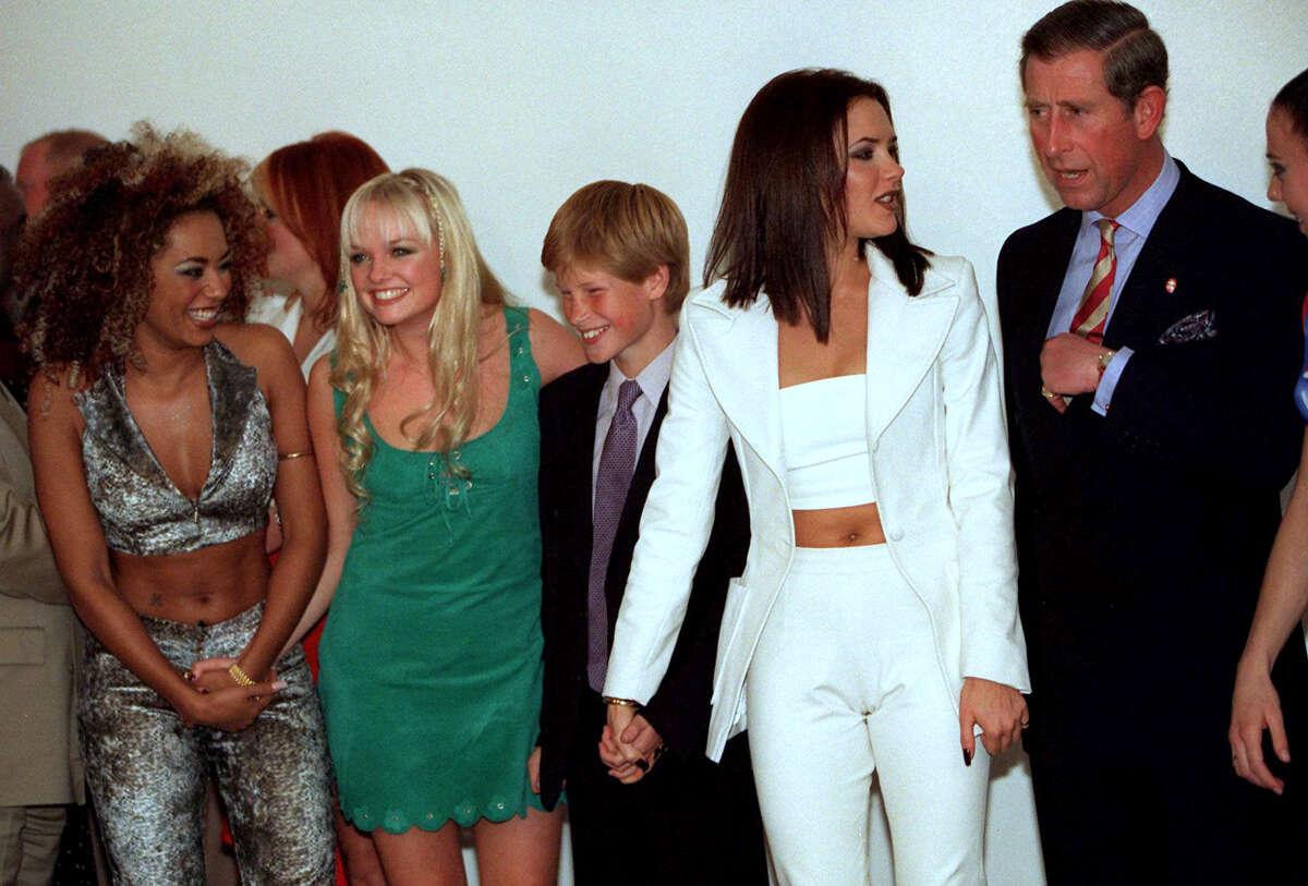Spice Girls members pose with Princes Charles and son Harry for photos prior to the group's performance Nov. 1, 1997 in Johannesburg. South Africa. From left are Mel B, Emma, Prince Harry, Victoria and Prince Charles.