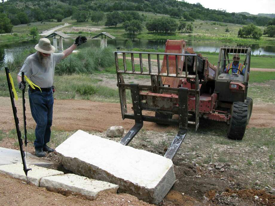 Steven Fleming (left) of the Kendall County Parks Department directs forklift driver Billy Shussler as he places a limestone block at Joshua Springs Park and Preserve. Photo: Zeke MacCormack, San Antonio Express-News / San Antonio Express-News