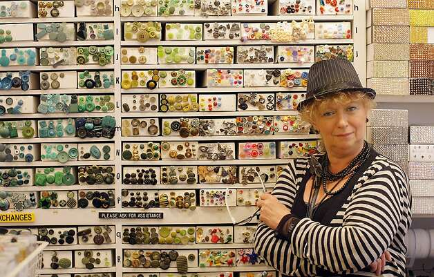 """Button Lady,"" Maya Gorokhovskaya take a brief moment to pose for a picture by the button's wall at Britex Fabrics store she works for 23 years on May 4, 2012. Britex was opened by Polish immigrants Martin and Lucy Spector in 1952 and it is family owned and managed by one of their daughters Sherman Spector. Some of the store employees had worked for the company for many years including Melody Doss, who has been with Britex for 33 years and Douglas Davis, who has been here for 23 years. Photo: Siana Hristova, The Chronicle"