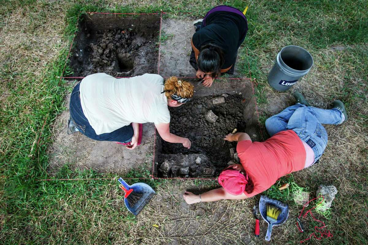 Jody Lawrence, left to right, Cindy Rodriguez and Elora Rowan excavate dirt as they and other students from the HCC Anthropology Department excavate the remains of a 100-year-old house in Freedmen's Town.