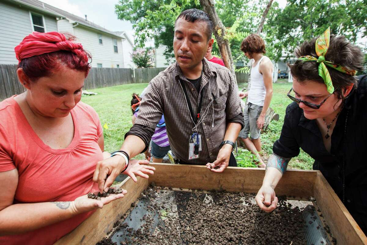 Elora Rowan, left to right, Alexander Hollis and Rachel Racz sift through excavated dirt as they and other students from the HCC Anthropology Department excavate the remains of a 100-year-old house in Freedmen's Town located in Houston's historic Fourth Ward, Thursday, June 28, 2012, in Houston.