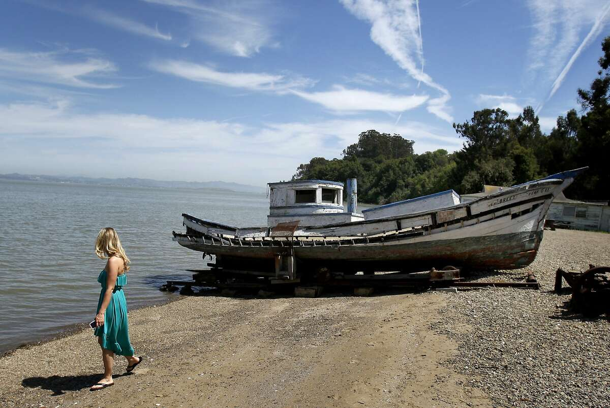 China Camp visitor Remy Wilson walks past one of the old shrimping boats on display on the beach. California State Senator Joe Simitian has unveiled a plan to save state parks including the popular China Camp State Park in Marin County, Calif.