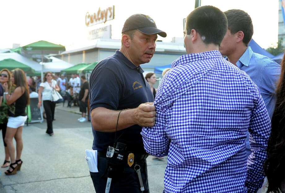 An attendee is held by the shirt sleeve after trying to run from Liquor Control Agents during Alive @ Five in Stamford's Columbus Park on Thursday, June 28, 2012. Photo: Lindsay Niegelberg / Stamford Advocate