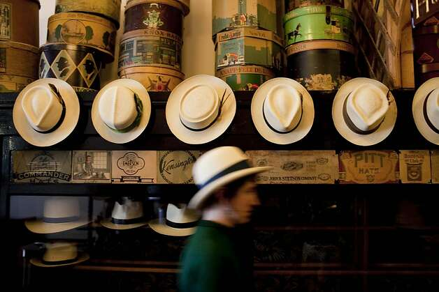 Abbie Dwelle walks past a row of hats at Paul's Hat Works. Photo: Stephen Lam, The Chronicle