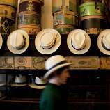 Abbie Dwelle walks past a row of hats at Paul's Hat Works.