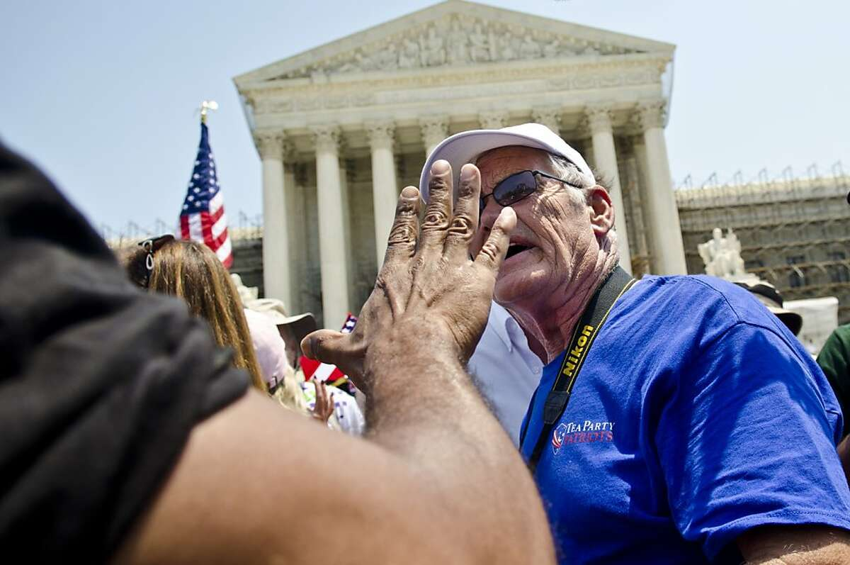 WASHINGTON, DC - JUNE 28: Protestors argue about the Affordable Healthcare Act outside the U.S. Supreme Court on June 28, 2012 in Washington, DC. The Court found the law to be constitutional and did not strike down any part of it. (Photo by Kris Connor/Getty Images) *** BESTPIX ***