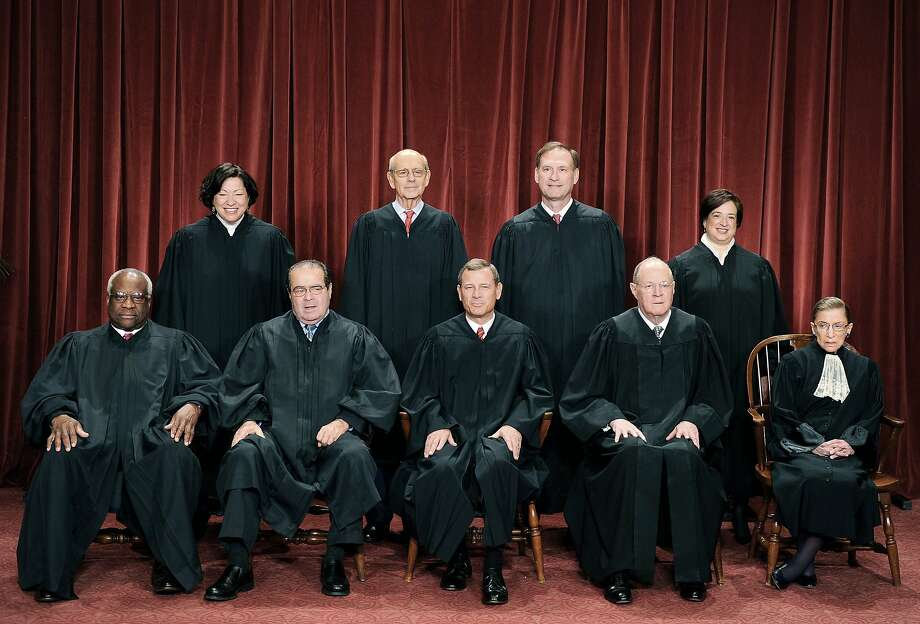 (FILES)The Justices of the US Supreme Court sit for their official photograph in this October 8, 2010 file photo at the Supreme Court in Washington, DC. The US Supreme Court struck down most of Arizona's controversial new immigration law on June 25, 2012, but let stand a key provision allowing officers to do spot checks of people's identity papers. The Arizona law has aroused intense controversy because of a particular provision, 2(B), that requires police to stop and demand proof of citizenship of anyone they suspect of being illegal, even without probable cause. Front row (L-R): Associate Justice Clarence Thomas,  Associate Justice Antonin Scalia, Chief Justice John G. Roberts, Associate Justice Anthony M. Kennedy and Associate Justice Ruth Bader Ginsburg. Back Row (L-R): Associate Justice Sonia Sotomayor, Associate Justice Stephen Breyer, Associate Justice Samuel Alito Jr. and Associate Justice Elena Kagan.   AFP PHOTO / TIM SLOAN/FILESTIM SLOAN/AFP/GettyImages Photo: Tim Sloan, AFP/Getty Images