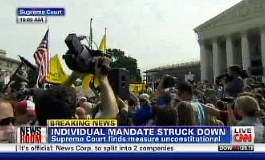 This television frame grab shows CNN broadcasting the Supreme Court's decision incorrectly on President Barack Obama's health care law on Thursday, June 28, 2012. Both CNN and Fox News Channel incorrectly reported Thursday that the law's central provision, requiring virtually all Americans to have health insurance, had been struck down. Both networks backtracked when it became clear that the court upheld the provision. Broadcast networks broke into regular programming to deliver special reports and generally got it right. To get the news out quickly, competitive news organizations had to wade through pages of legal writing. (AP Photo) Photo: Associated Press