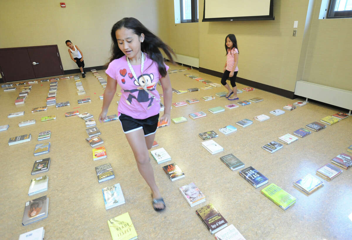 From left, Manuel Estrada, 9, of Albany, Alyanna Leandry, 11, of Latham and her cousin Alyssa Lay, 7, visiting from Boston, find their way through a giant indoor labyrinth lined by books at the Albany Public Library John A. Howe Branch Thursday, June 28, 2012 in Albany, N.Y. (Lori Van Buren / Times Union)