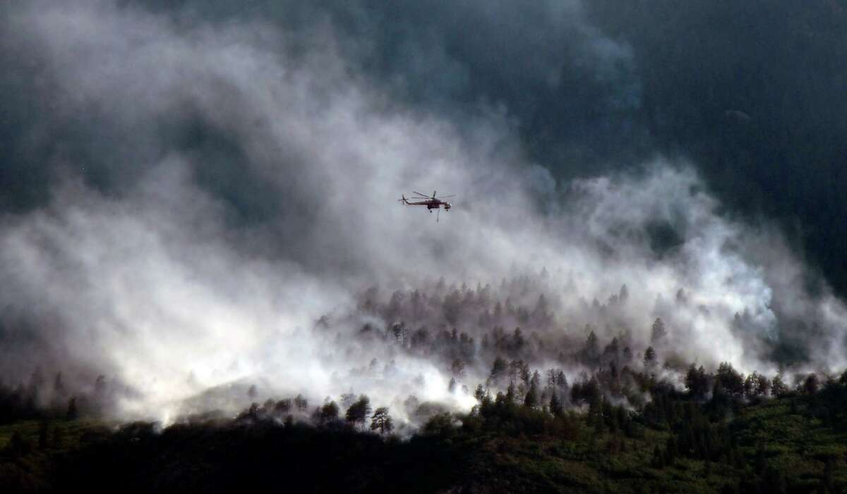 A helicopters flies over as the Waldo Canyon Fire continues to burn Wednesday, June 27, 2012, in Colorado Springs, Colo. The wildfire doubled in size overnight to about 24 square miles (62 square kilometers), and has so far forced mandatory evacuations for more than 32,000 residents. (AP Photo/Bryan Oller)