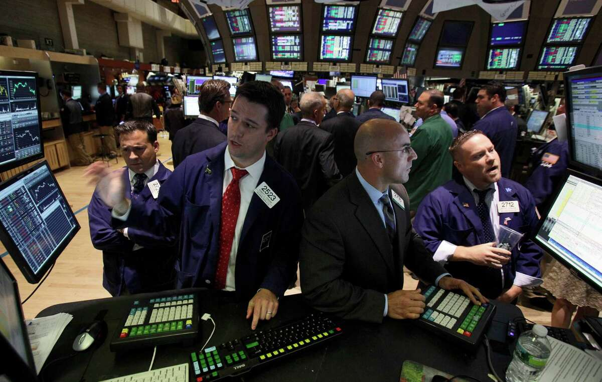 Specialists Robert Canzani, left, and Henry Becker, second from right, work at their posts on the floor of the New York Stock Exchange Thursday, June 28, 2012. Stocks dropped sharply Thursday after the Supreme Court upheld the central provision of President Barack Obama's health care overhaul, a requirement that almost all Americans carry health insurance. (AP Photo/Richard Drew)